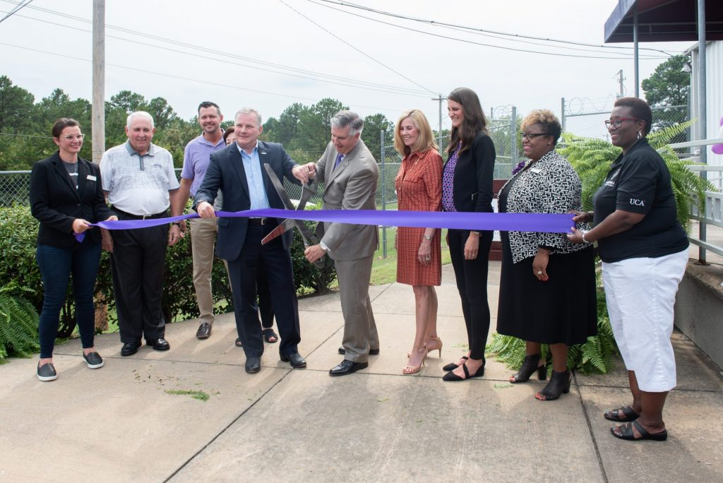 Ark. Lt. Gov. Tim Griffin and UCA President Houston Davis (center) cut a purple ribbon at the grand opening of the new Arkansas Coding Academy campus Thursday. They are joined by several UCA Board of Trustees members and employees.